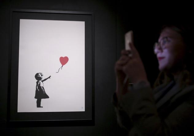 """One of Banksy's """"Girl With Balloon"""" paintings is on display at an exhibition opening of works by the England-based street artist, at St. Petersburg's Manege Central Exhibition Hall in September."""