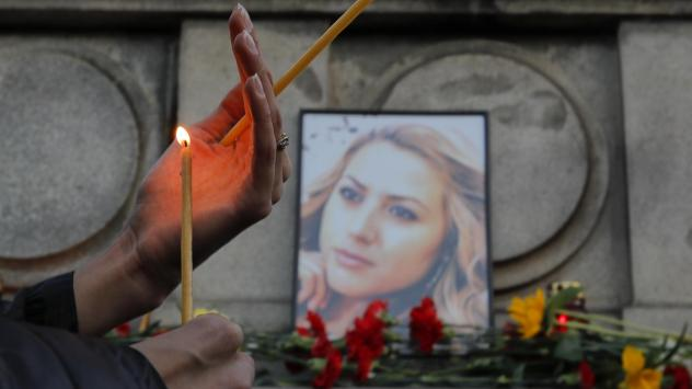 A woman holds a candle next to a portrait of slain journalist Viktoria Marinova during a vigil at the Monument of Liberty in Ruse, Bulgaria, on Monday.