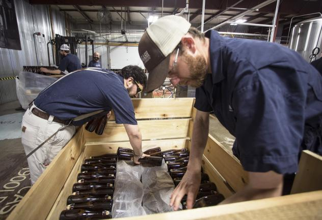 Allagash employees Salim Raal, left, and Brendan McKay stack bottles of Golden Brett, a limited release beer fermented with a house strain of Brettanomyces yeast. The Maine brewery recently installed solar panels as part of its sustainability initiatives