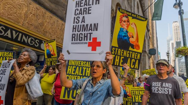 Activists march to the offices of Sens. Chuck Schumer and Kirsten Gillibrand in New York City in September 2017, just before the start of Senate hearings on stabilizing the Affordable Care Act.