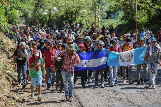 Migrants heading toward the U.S. carry Honduran and Guatemalan national flags in Guatemala on Monday. President Trump has threatened to cut off aid to Honduras, Guatemala and El Salvador for failing to stop the caravan's journey.