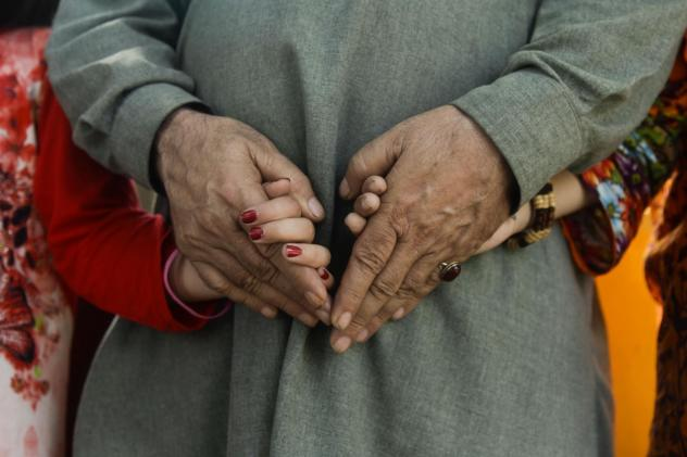 "Mir, a Pakistani man who used to live in Xinjiang, China, clutches the hands of his two daughters. Since Chinese authorities detained his wife, he's been raising their two girls alone. ""My mind just won't work,"" he says. ""I sound incoherent, I can't thin"