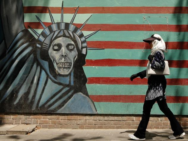 An Iranian woman walks past the former U.S. Embassy in Tehran, which bears a mural depicting the Statue of Liberty with a dead face. With just days to go until the U.S. plans to snap more sanctions back into place, questions linger about what the move sp