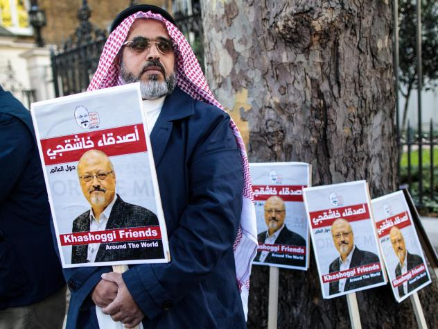 Jamal Khashoggi's fiancee and others will speak about his life and legacy on Friday, one month after he was killed in Saudi Arabia's consulate in Istanbul. Here, a protester holds a placard showing solidarity for Khashoggi during a demonstration outside
