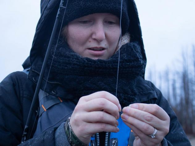 Kristy Taylor baits her hook while fishing on the Two Hearted River in Michigan. She's part of a steelhead fishing class put on by the Michigan Department of Natural Resources in an effort to inspire more women to fish.