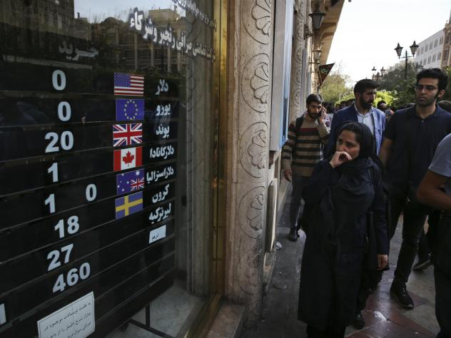 An exchange shop displays rates for various currencies in downtown Tehran last month. Iran is bracing for the restoration of U.S. sanctions on its vital oil industry set to take effect on Monday, as it grapples with an economic crisis that has sparked sp