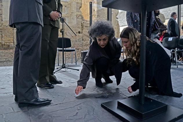 Colombian sculptor Doris Salcedo (center) cleans a spill on the floor during the pre-inauguration of her peace monument titled <em>Fragmentos</em> (Fragments), for which she used metal melted-down from the weapons handed over by FARC guerrilla fighters t