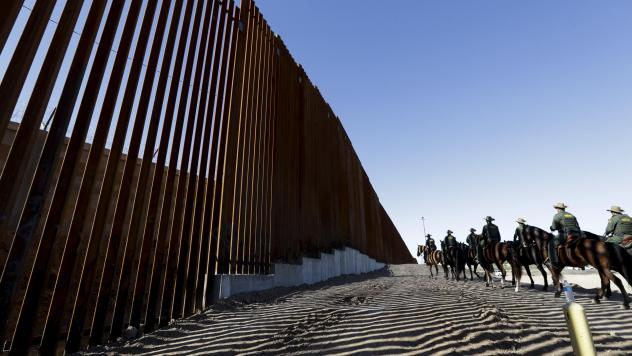 Mounted Border Patrol agents ride along a newly fortified border wall structure in Calexico, Calif. Funding for the border wall is one of a number of administration priorities that may face challenges if the Democrats flip the house.