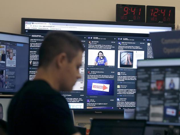 A man works at his desk in front of monitors last month during a demonstration in the war room, where Facebook monitors election-related content on the platform, in Menlo Park, Calif.