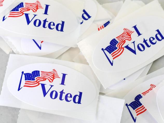 """""""I voted"""" stickers pile up Tuesday at a polling station in Irvine, Calif. Across the country, in Rochester, N.Y., voters found a fitting use for their own stickers: placing them on the headstone of suffragist Susan B. Anthony."""