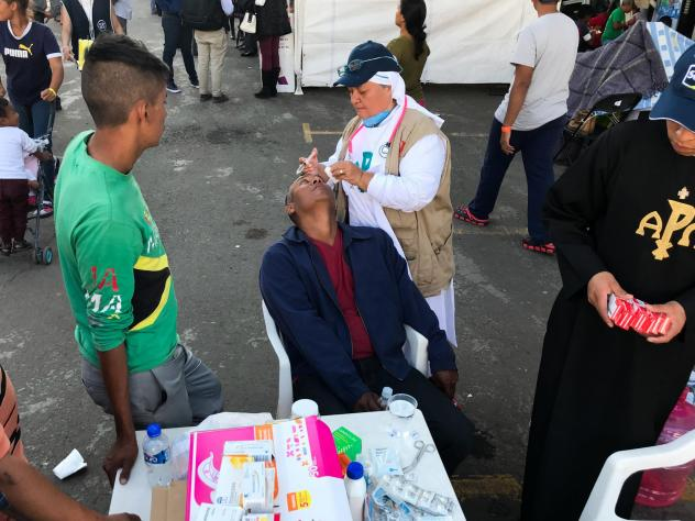 "Sister Bertha Lopez Chaves applies anti-inflammatory eyedrops to a migrant at a stadium in Mexico City where the caravan is resting. Her order is one of roughly 50 groups giving aid to the migrants in the Mexican capital. ""We're just trying to deal with"