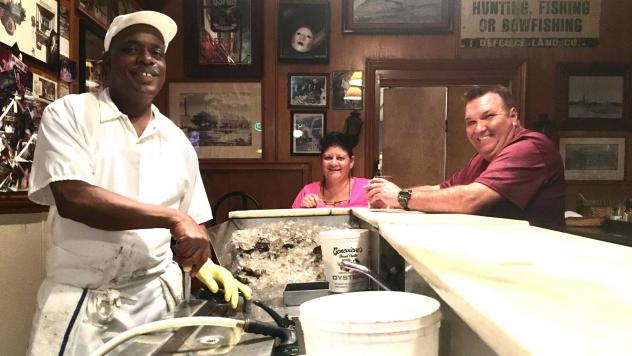 "<a href=""http://mediad.publicbroadcasting.net/p/wwno/files/styles/x_large/public/201811/img-6038_1__1.jpg""> </a> Thomas ""Uptown T"" Stewart (left), has been shucking oysters at Pascal's Manale restaurant for more than 30 years, about as long as Paula (mid"