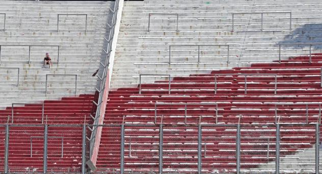 A River Plate fan sits on an empty stand at the Monumental Stadium in Buenos Aires, after the all-Argentine Copa Libertadores second leg final match against Boca Juniors was postponed on Sunday for the second time following an attack on the Boca team bus