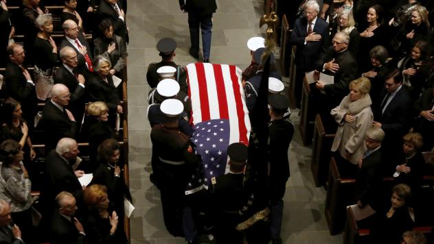 The flag-draped casket of former President George H.W. Bush is carried by a joint services military honor guard into St. Martin's Episcopal Church Thursday, Dec. 6, 2018, in Houston. (AP Photo/Mark Humphrey)