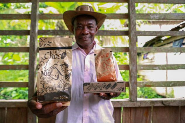 José Palacios, a cacao farmer, holds the Late Chocó chocolate products produced by his son, Joel, in Bogotá. The package bears an illustration of his likeness. José Palacios lives in Colombia's western Chocó department, which is also a coca-growing
