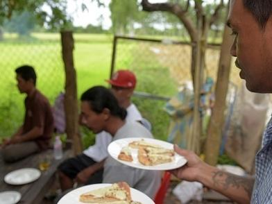 Nheb Thai, a Cambodian refugee who was deported from the U.S., serves a meal to other deportees in Battambang last year. Cambodia has taken in 566 deportees since inking a 2002 pact with the U.S. that opened the door for hundreds with criminal records to