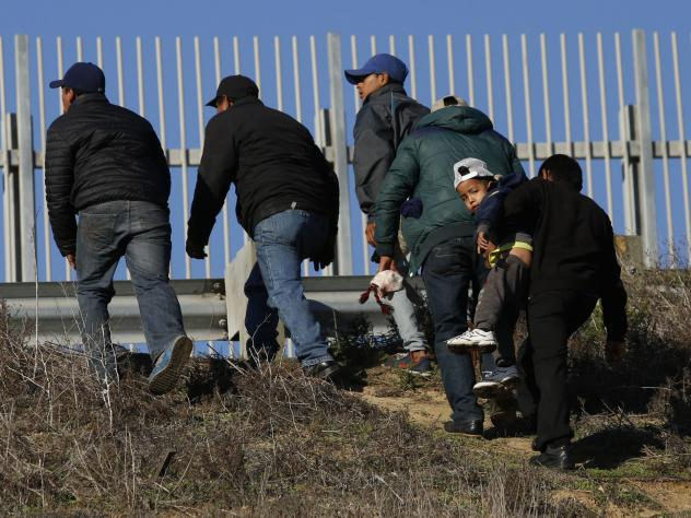 Migrants, one carrying a child, who plan to turn themselves over to U.S. border agents, walk up the embankment after climbing over a U.S. border wall from Playas de Tijuana, Mexico, last week. On Tuesday, members of the Hispanic Caucus called for improve