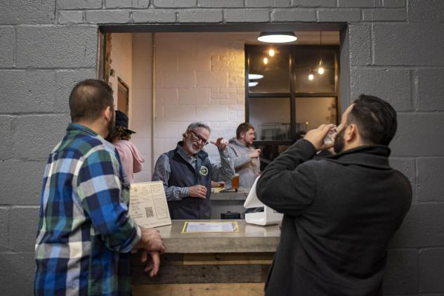 "Co-founder Mark Burke signs with patrons at Streetcar 82 Brewing Co., in Hyattsville, Md. ""My goal is to make the best beer,"" Burke said. ""But the impact and magnitude of how this influences the Deaf community is inspiring."""
