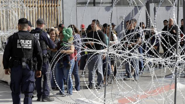 People line up to cross into the United States from Tijuana, Mexico, seen through barriers topped with concertina wire at the San Ysidro Port of Entry in San Diego. A federal judge on Wednesday blocked the administration from enforcing a ban on asylum-se