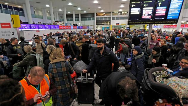 Passengers wait in Gatwick Airport after the airport was forced to shut down operations due to drones that flew illegally over its airfield Thursday.