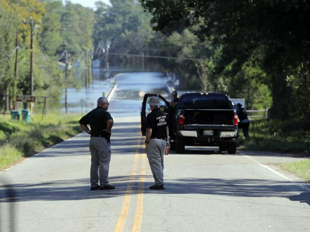 Officers stand near where two people drowned in a Horry County Sheriff's transport van overturned by floodwaters in South Carolina.
