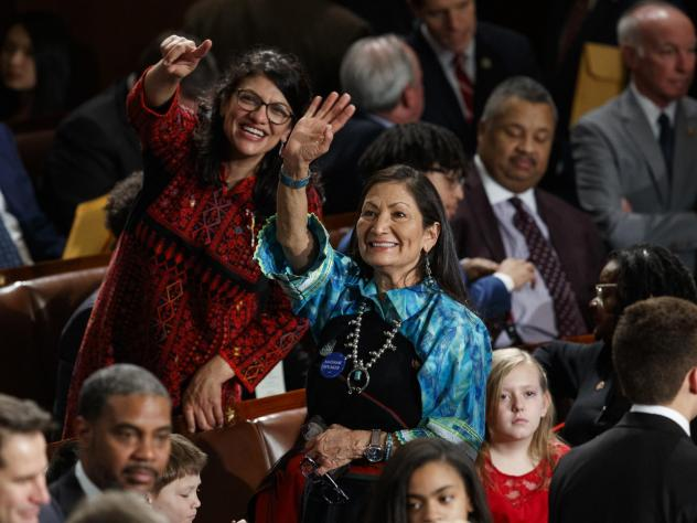Rep. Rashida Tlaib (D-Mich.) left, and Rep. Deb Haaland, (D-N.M.) look up to the gallery at the U.S. Capitol on the day they are sworn in as members of Congress.
