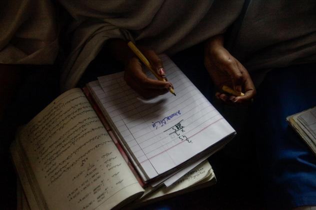 A student takes notes in a math class in the Government Girls High School of Meer Muhammad.