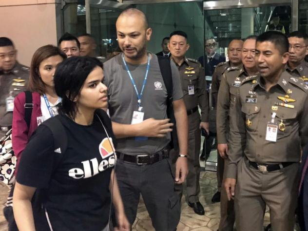 Saudi woman Rahaf Mohammed Alqunun walks by Thai Chief of Immigration Police Maj. Gen. Surachate Hakparn (right) before leaving the Suvarnabhumi Airport in Bangkok. Australia says it is considering granting refugee resettlement to the Saudi, who fled fro