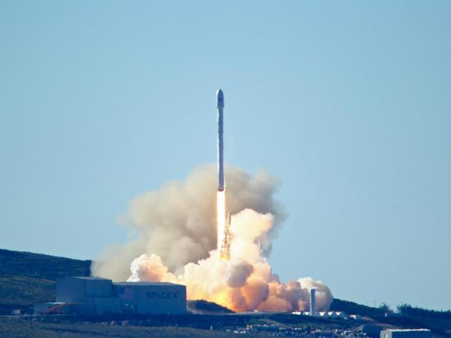 Space-X's Falcon 9 rocket with 10 satellites launches at Vandenberg Air Force Base, Calif., in 2017. The company says it will lay off 10 percent of its workforce.