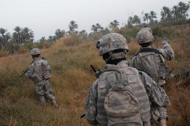 U.S. soldiers traverse fields on the way to conducting house-to- house searches in 2007 in Mukhisa, Iraq.