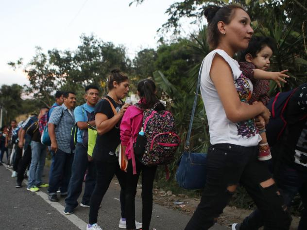 Honduran migrants wait in line to cross over the border checkpoint into Guatemala in Agua Caliente, Honduras. A new caravan of at least several hundred Hondurans has set off toward the United States on foot or in vehicles. Some have already crossed into