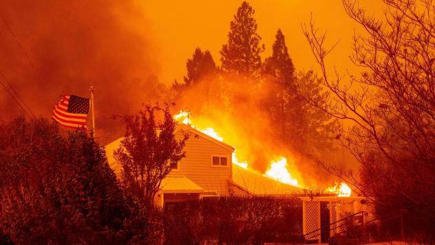 """A home burns during the Camp Fire in Paradise, Calif., in November 2018. It was one of several fires often discussed in terms of the changing climate. A new survey shows a jump in the number of Americans who are """"very worried"""" about global warming."""