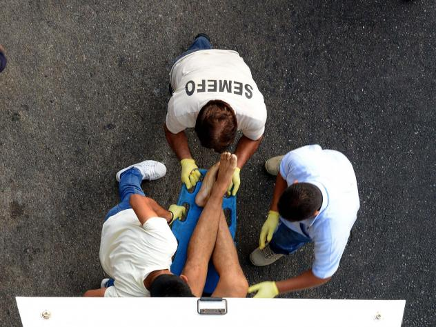 Forensic personnel load the corpse of a man into a van, after he was executed at a shopping mall in Acapulco, Mexico, on April 24, 2018. A new report recorded more than 33,000 homicides in 2018, making it the country's deadliest on record.