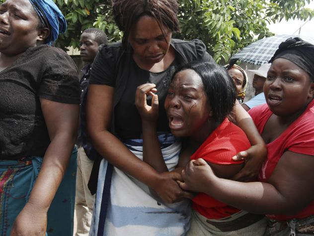 A family member of Kelvin Tinashe Choto reacts, during his funeral in Chitungwiza, about 30 kilometres south east of the capital, Harare, Zimbabwe on Saturday. The 22-year-old was shot in the head, one of at least a dozen people killed in a violent crack