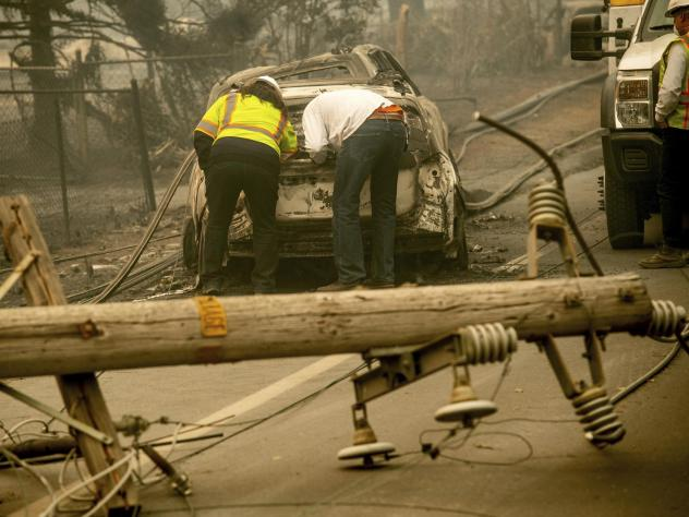 With a downed power utility pole in the foreground, residents of Paradise, Calif., examine a burned-out vehicle destroyed by last year's wildfire.
