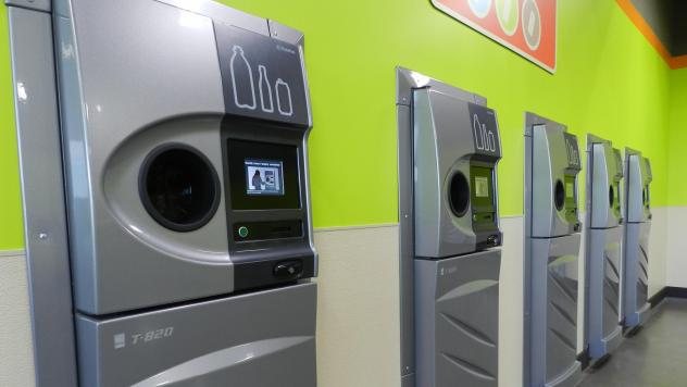 A row of new reverse vending machines, which collect drink containers for recycling, greets customers at the grand opening of the BottleDrop Redemption Center in Medford, Ore.