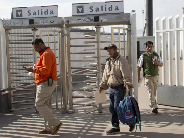 Carlos Catarldo Gomez, of Honduras, center, is escorted by Mexican officials after leaving the United States, the first person returned to Mexico to wait for his asylum trial date, in Tijuana, Mexico