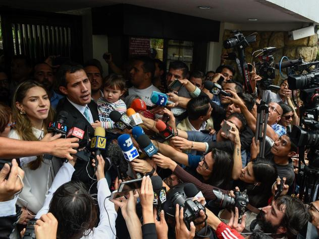 Opposition leader Juan Guaidó talks to the press as he holds his daughter, Miranda, next to his wife, Fabiana Rosales, outside his home in Caracas on Thursday.