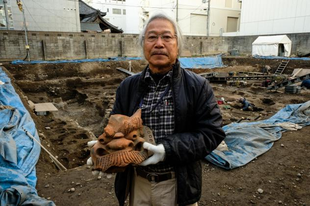 Archaeologist Koji Iesaki holds a carved roof ornament excavated at the former site of the Jyokyo-ji temple in Kyoto. Iesaki and other archaeologists have their hands full, as a pre-Olympic building boom has helped reveal centuries-old artifacts from the