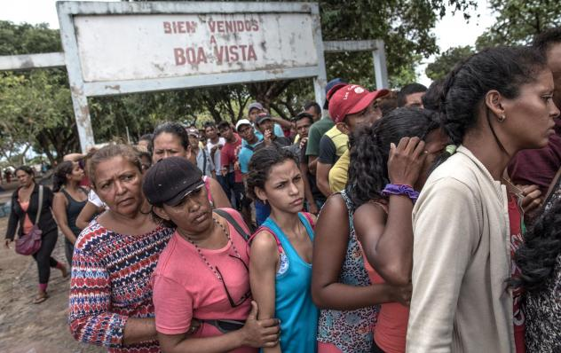 Venezuelans wait in line for food in northern Brazil. The migrants often say the main reasons they've fled are to get food and health care.