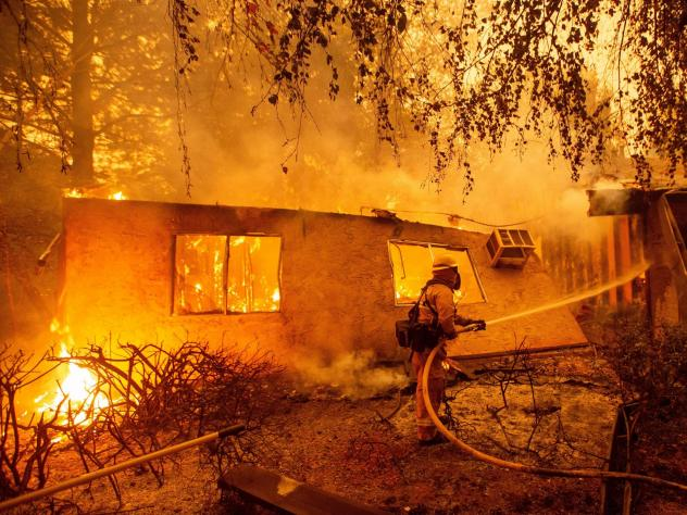 Firefighters battle flames at a burning apartment complex in Paradise, Calif., in November. PG&E could shut down power to as many as 5.4 million customers during extreme weather conditions.