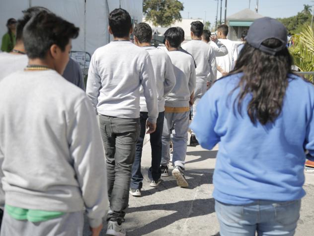 Nearly 1,600 teenage migrants are housed at a temporary emergency shelter in Florida run by a for-profit company.