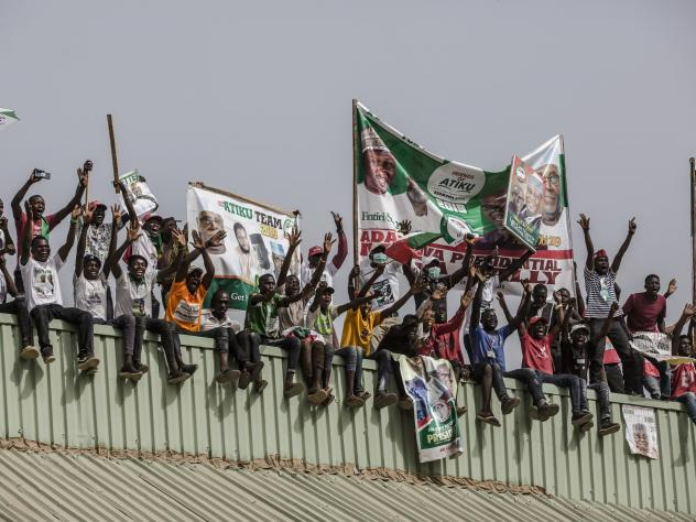 Supporters stand on a roof with placards and banners as they attend the final campaign rally of the Nigerian opposition leader Atiku Abubakar on Thursday in Jimeta, eastern Nigeria.