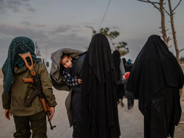 Veiled women reportedly associated with ISIS walk under the supervision of a female fighter from the Syrian Democratic Forces in northeastern Syria on Sunday. Over the weekend, President Trump demanded European allies repatriate their citizens captured a