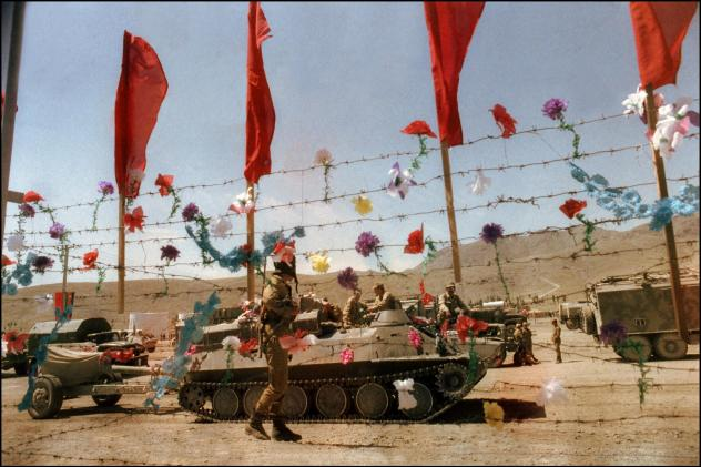 Artificial flowers decorate barbed wire fence as Soviet army troops stop in Kabul, Afghanistan, in May 1988. The Soviet Union invaded Afghanistan in December 1979 to shore up the pro-Soviet regime in Kabul.