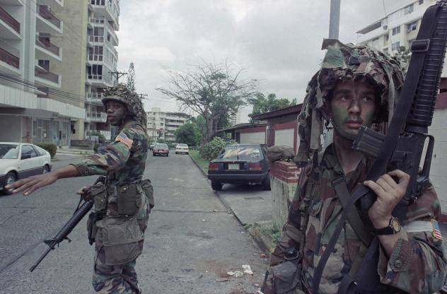 U.S. soldiers direct traffic outside the residence of the Peruvian ambassador to Panama, right rear, in Panama City on Jan. 9, 1990. In December 1989, U.S. President George H.W. Bush sent thousands of troops to Panama to arrest the country's leader, Manu