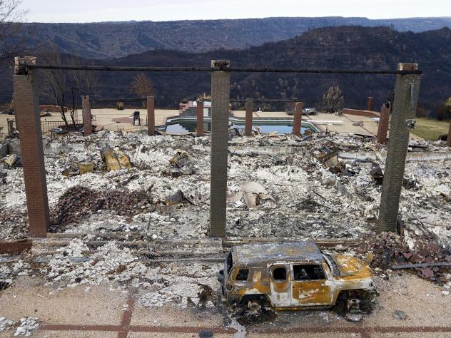 A vehicle rests in front of a home leveled by the Camp Fire in Paradise, Calif., in a photo from December. Pacific Gas & Electric says its equipment may have ignited the 2018 fire.