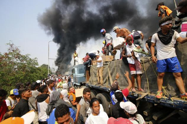 People try to salvage humanitarian aid after the truck carrying it was set ablaze on the Francisco de Paula Santander International Bridge between Colombia and Venezuela on Feb. 23.