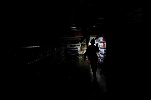 A worker inspects damage in a supermarket in Caracas on Sunday after it was looted during Venezuela's dayslong blackout.