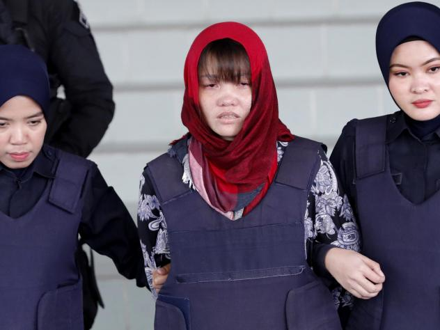 Vietnamese Doan Thi Huong, center, is escorted by police as she leaves Shah Alam High Court in Malaysia on Thursday. Malaysia's attorney general ordered the murder case to proceed against the Vietnamese woman accused in the killing of the North Korean le